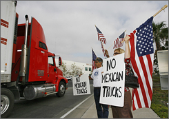 Robin Hvidston, right, and Raymond Herrera, center, protest as a truck entering the U.S. from Mexico leaves the California Highway Patrol Otay Mesa Inspection Station Thursday in San Diego.
