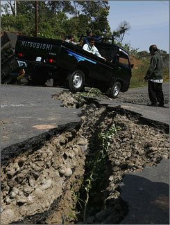 A vehicle drives near a damaged road at Serangai village near the Indonesian city of Bengkulu, Friday.
