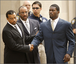 Attorney Billy Martin, left, shakes hands with client Michael Vick last month as the NFL star arrives at federal court in Richmond, Va.