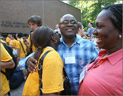 Family hug: Ade and Funmi Alakija, from Lagos, Nigeria, attend parent-student orientation at Boston College with their daughter, freshman Toyin Alakija.