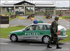 German police and U.S. soldiers block the street in front of the main entrance of U.S air base in Spangdahlem, western Germany, Tuesday. A man called the air base and threatened to attack it, prompting police to step up security measures.
