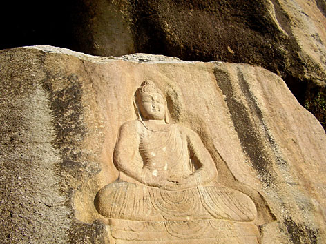 A survived statue of  Buddha carved into a rock is seen in Jehanabad, 118 miles north of Peshawar, Pakistan, Wednesday. Islamic militants tried to blow up the ancient statue of Buddha carved into the mountainside in northwestern Pakistan, but did not damage the structure, officials and witnesses said Wednesday.