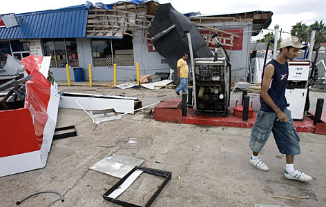 The owners of a gas station walk through the wind damaged remains of their business Friday in High Island, Texas. Many residents of High Island were still rebuilding after Hurricane Rita in 2005 caused severe damage to many businesses and homes before Humberto swept through on Thursday.