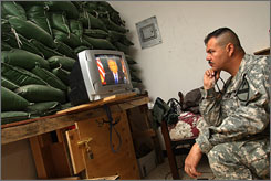 1st. Sgt. Kenny Power, from Lajas, Puerto Rico, watches Bush's address on withdrawing troops via satellite TV in Baghdad.