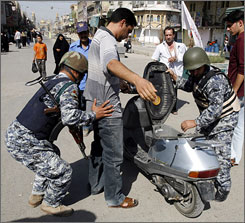 Iraqi police officers search a man in the Shiite Kazimiyah neighborhood of Baghdad on Friday.