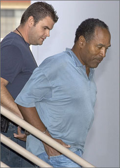 A Las Vegas Metropolitan Police detective escorts O.J. Simpson from the police robbery offices as he is taken to the Clark County Detention Center in Las Vegas on Sunday.