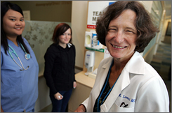 Dr. Joyce Lammert, right, meets with medical assistant Giselle DeMesa, left, and patient Brittany English at a flu kiosk at Virginia Mason Medical Center in Seattle.