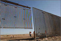 Contractors install sections of fencing near Calexico, Calif. The barrier is part of the Bush administration's plans for more than 700 miles of new fencing along the U.S.-Mexican border.