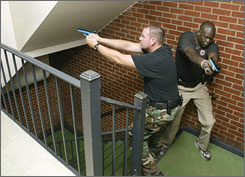 Austin Peay State University police officers Timothy Adair, left, and Piot Bol clear a stairway during a mock shooting training session on campus this July, which included city and campus police.