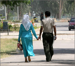 A couple holds hands as they walk through Zawraa, Baghdad's largest park, in June.