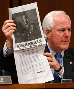 Sen. John Cornyn, R-Texas, holds up a copy of an ad paid for by MoveOn.org during a hearing of the Senate Armed Services Committee with Gen. David Petraeus and U.S. Ambassador to Iraq Ryan Crocker on Capitol Hill September 11 in Washington.