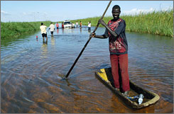 A man pushes himself along a submerged highway in a canoe in Soroti, Uganda, 168 miles northeast of the capital city Kampala on Thursday. Torrential floods have killed at least 200 people in East and West Africa in recent weeks.