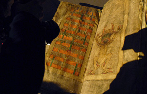 A visitor looks at the Devil's Bible during an opening of an exibition at the Czech National Library in Prague, Wednesday. The manuscript was written in the early 13th century in the Benedictine monastery of Podlazice in Bohemia, and during the Middle Ages was regarded as a wonder of the world.