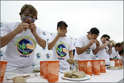 "Tim Janus, left, known as ""Eater X,"" Sonya Thomas, known as ""The Black Widow,"" Mike Babich, and Bill Meyers, participate in the world-burrito eating championship in Maine."