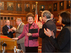 New York Chief Judge Judith Kaye, center, applauded after giving a speech in 2005, has threatened to sue the Legislature and governor over judicial pay raises.