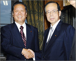 Newly-elected Japanese Prime Minister Yasuo Fukuda, right, shakes hands with main opposition Democratic Party leader Ichiro Ozawa after Fukuda was elected prime minister, at the parliament in Tokyo, Tuesday.