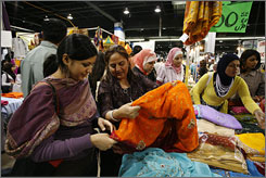 Sarah Uddin, left, and her mother, Naseem, shop for saris at the Islamic Society of North America's conference, where attendees could buy anything from clothing to Qurans at a huge bazaar.