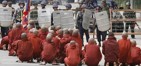 A group of monks sit in protest after being halted by riot policemen and military officials as they attempt to proceed to the Shwedagon Pagoda in Rangoon, Wednesday.