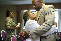 Elliott Thompson, a pastor and Army reservist, hugs his wife, Gail, during services at Christ for Life International Ministries in Sharonville, Ohio. He was one of about 10,000 people who filed a housing discrimination complaint last year.