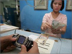 Dennis Tiangco receives money at a bank that was sent by his mother in Hong Kong thru his cell phone in San Miguel town, in the northern Philippines. More than 5.5 million Filipinos now use using their cell phones as virtual wallets.