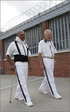 "Prisoners Joe Williams, left, and Manson Robert Griffin walk in the ""yard area"" of a state prison in Hardwick, Ga. ""It's heart-rending to see some of the older people in the condition they're in,"" Griffin says. ""You have to wonder why they haven't had a little leniency on them to let them go home?"""