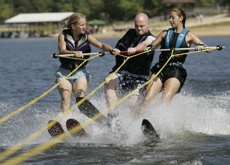 Marine Daniel Ribbentrop of San Antonio water-skis single-handedly with camp aides Heather Pennington, left, and Keri Petrofsky.