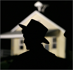 Amish men gather outside the schoolhouse where a gunman killed five girls and then himself on Oct. 2, 2006 in Lancaster County, Pa..