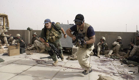 Plainclothes contractors working for Blackwater USA take part in a firefight as Iraqi demonstrators loyal to Muqtada al-Sadr attempt to advance on a facility being defended by U.S. and Spanish soldiers in this April 2004 file photo taken in the Iraqi city of Najaf.