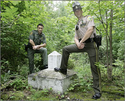 Vermont State Police Trooper John MacCallum, right, and U.S. Border Patrol Agent Matt Hayes. left, stand at a marker on the U.S.-Canada border in Highgate, Vt. Increasingly, the Border Patrol is assisting the Vermont State Police, not only in manpower but with equipment such as patrol aircraft.