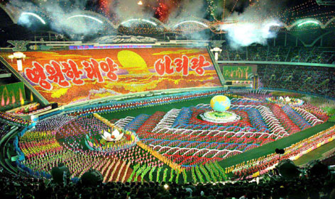 """A cast of tens of thousands performs in the Arirang Festival at May Day Stadium in Pyongyang on Wednesday. The extravaganza extols North Korea's leadership and communist ideology. The flip cards, held by children, proclaim """"Never-setting sun"""" and """"Proud of our country."""""""