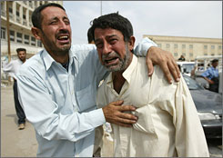Iraqi relatives cry near a truck carrying bodies of victims of a U.S. air raid on the village of Al-Jayzani, near Baquba on Friday as they drive them to be buried in the Shiite holy city of Najaf.
