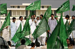 Supporters of Pakistan's military ruler Gen. Pervez Musharraf wave Pakistan's Muslim League flags before President House to celebrate the Supreme Court decision in Islamabad, Pakistan, Friday.