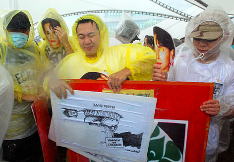 Protesters hold posters against a powerful gust of wind generated by Typhoon Krosa during a rally to protest against Burma's recent crackdown on pro-democracy demonstrators, Saturday, in Taipei, Taiwan.