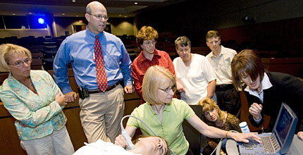 Nurse practitioner Joan Anderson, center, gets trained to use an ultrasound scanner in Madison, Wis.