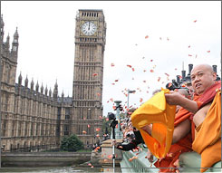 U Uttara, right, Britain's leading Burmese monk, releases petals into the River Thames from Westminster Bridge.