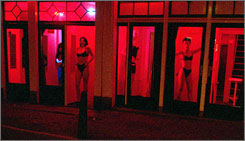 Prostitutes wait for customers behind brothel windows in Amsterdam's central redlight district, known as the Wallen. The city plans to buy out about a third of the brothels in the district.