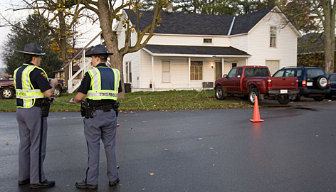 Wisconsin state troopers stand guard in front of a house in Crandon on Monday morning. The community of 1,961 residents, about 105 miles northwest of Appleton in an area known for logging and outdoor activities, is facing a trying time but is pulling together, Mayor Gary Bradley said.