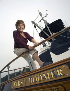 "Kathleen Casey-Kirschling  will get her first Social Security check in January. The occasion will be one small step for her, one giant leap for her generation.   She is photographed on the back of her boat ""First Boomer."""