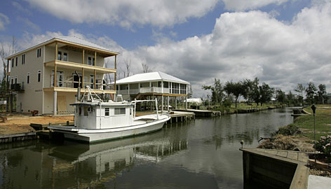 "Finley and Laurie Williford's home, left, is under construction on a canal in Bay St. Louis, Miss. ""If they had showed up a day after the storm, I probably would have taken the money. It's kinda after-the-fact now,"" Williford said."