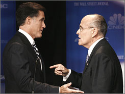 Mitt Romney talks with Rudy Giuliani after the Republican presidential debate in Dearborn, Mich.
