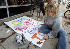 Haley Fehrenbach, 16, makes a sign to hang in the store window of Flowers From The Heart in downtown Crandon to support the families of the shooting victims.