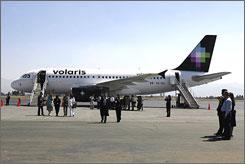Visitors observe a Volaris airplane at the Ciudad de Toluca airport, Mexico.