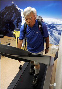 Yuichiro Miura wears a 44-pound backpack as he strolls on a treadmill against a photo panel of Mount Everest in a $260,000 low-oxygen room that he had built inside his Tokyo home to help him acclimatize to thin air. Miura's planned climb is estimated to cost around $1.7 million spanning three years to 2008.