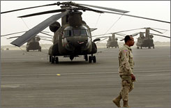 Army Lt. Col. Leon Sumpter walks past helicopters at Camp Arifjan in Kuwait in June 2003. The Pentagon is investigating corruption at the base, the center of the Army's financial operation for Iraq.