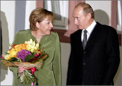 Russia's President Vladimir Putin is welcomed by German Chancellor Angela Merkel in Hattenheim, Germany, Sunday. Putin is on a two-day visit to Germany for talks between Germany and Russia.