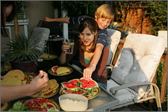 Carson Predovich, 11, reaches around his sister Sierra for a piece of watermelon during dinner.