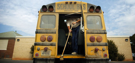 Travis Woodford sweeps out his Bedford County, Va., bus after pressure washing it Wednesday, two days after a student died of a staph infection. After a student protest, officials shut down 21 schools for cleaning to keep the illness from spreading.