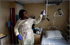 Shaquina Davis wipes down a patient's room with disinfectant Wednesday at the Miami VA Medical Center. The hospital has strict policies to ensure the staff uses procedures in the fight against MRSA.