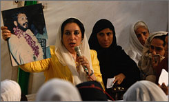 Former Pakistani prime minister Benazir Bhutto holds a photograph of a victim of the bomb attack aimed at her three days ago during a prayer session in the victims' memory at  Bhutto's house in Karachi, Pakistan.