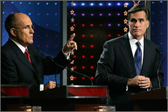 Mitt Romney, right, listens as Rudy Giuliani makes a point during the Republican debate in Orlando.